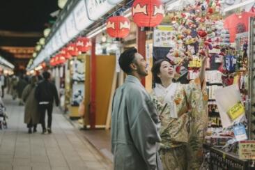 和装を着て夜の浅草商店街を楽しむ二人