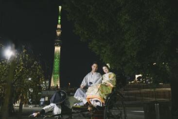 夜のイルミネーションが綺麗なスカイツリーと和装を着て人力車に乗った2人