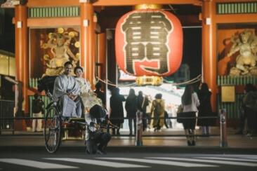雷門の前で人力車に乗っている紋付と色打掛を着た新婚カップル