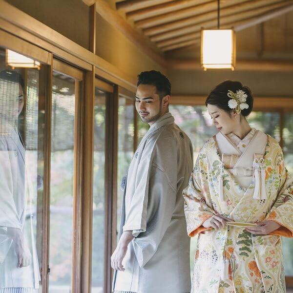 目白庭園の縁側に立っている和装姿の二人