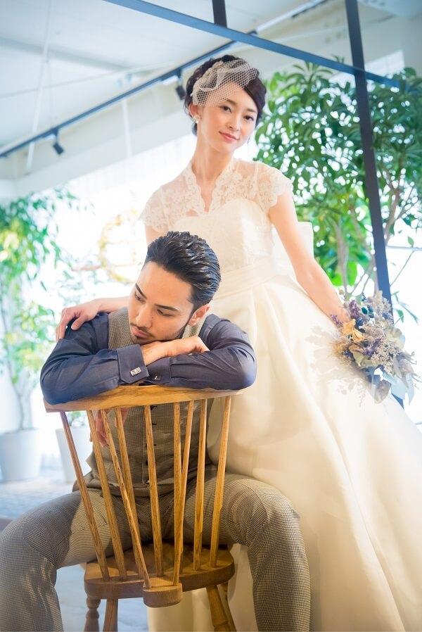 椅子に座った新郎と新郎の肩に手をそれる新婦