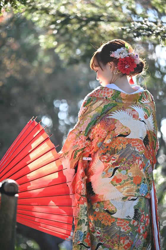 色打掛を着て赤の和傘を持った新婦