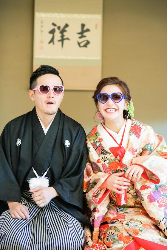 ハートのサングラスをかけて笑顔の夫婦
