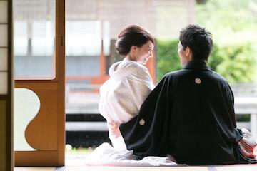縁側に座る白無垢と紋付を着た夫婦