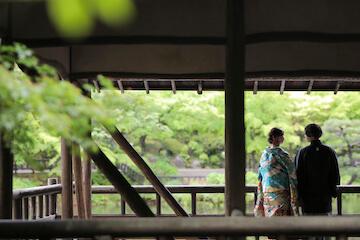 景色がきれいな庭園に立つ青の色打掛を着た新婦と黒の紋付姿の新郎