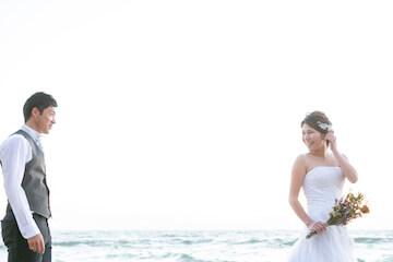 海でお互いを見てウェディング写真を撮っている二人
