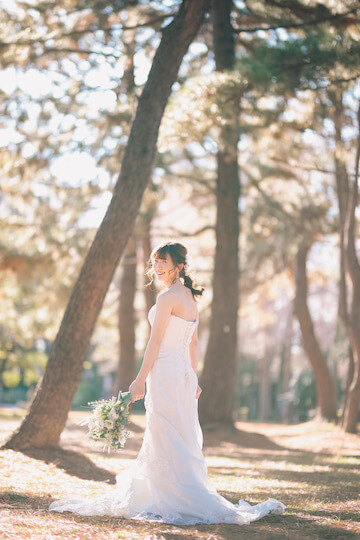 西日がさす中、笑顔で振り返る花嫁