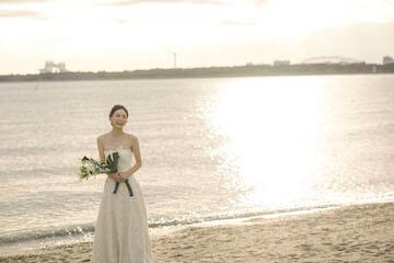 葛西海浜公園の夕日をバックに笑顔の花嫁