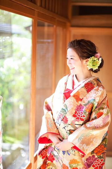 オレンジの打掛を着て笑顔の花嫁