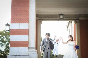 ドレスを着たお母さんとタキシードを着たお父さんと、真ん中で手を繋いでジャンプしている息子