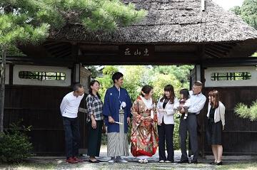 茶室の入り口の前で集合写真を撮影している家族