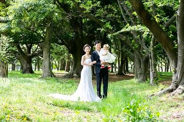 公園に立つ洋装姿の家族3人