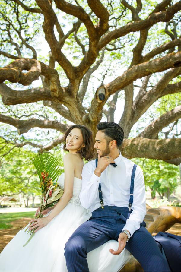 木が特徴的なロケーションでウェディング衣装を着て座っているふたり