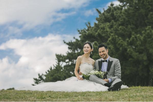 葛西臨海公園に丘に座っているドレスと千鳥柄のタキシードを着たふたり