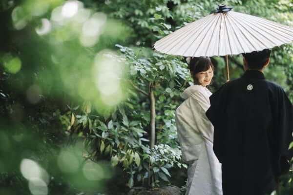 白い和傘を指している白無垢を着た花嫁と新郎