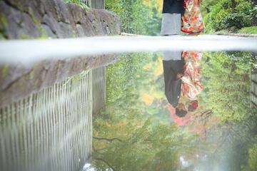雨の日に水たまりに移る和装姿のふたり