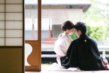 白無垢と黒紋服を着た縁側に座る夫婦