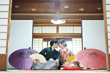 お茶室に座る新郎新婦と和傘