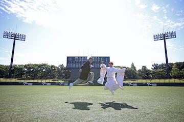 野球場の真ん中でジャンプしてる2人