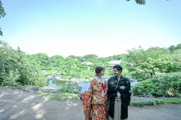 壮大な日本庭園の前に並ぶ紋付と色打掛を着た夫婦