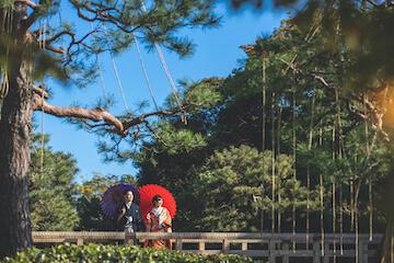 日本庭園が美しいロケ地で和装を着て橋の上に立つふたり