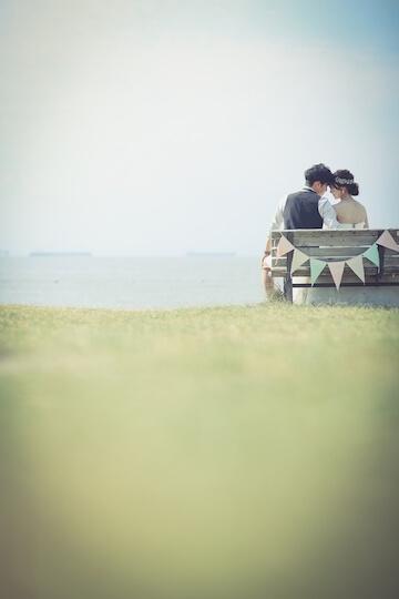 海辺のベンチに座るカップル