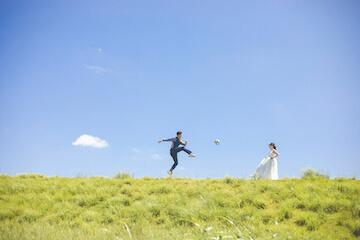 結婚写真を撮りながらサッカーを楽しむふたり