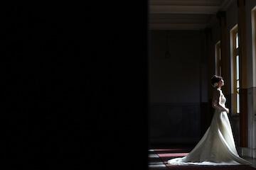 暗い空間の中光の射す窓を見ている花嫁