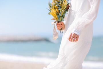 ビーチでドライフラワーブーケをもって、カジュアルなウェディングドレスを着ている花嫁さん