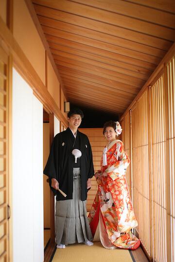 お茶室で和装のきれいな立ち姿で並んでいる新郎新婦
