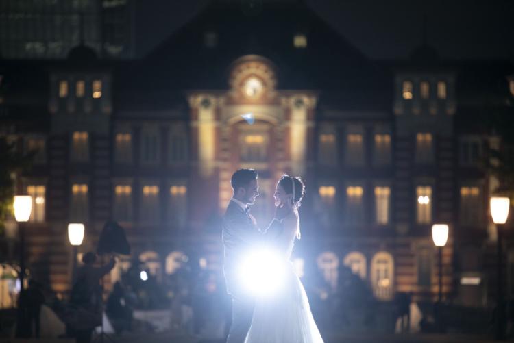 夜の綺麗な東京駅をバックに向かい合って結婚写真を撮るふたり