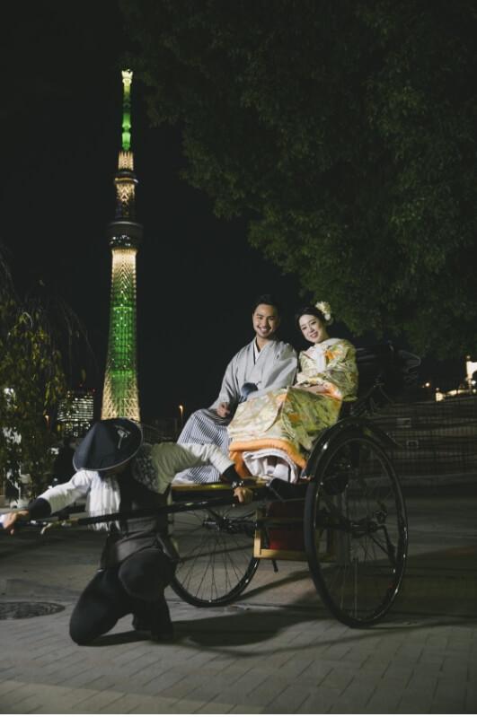 スカイツリーが綺麗に見えるスポットで人力車に乗っている和装姿の新婚夫婦