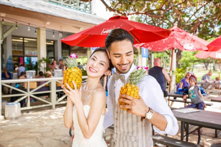 ハワイでパイナップル丸ごとジュースを持って笑顔のカップル