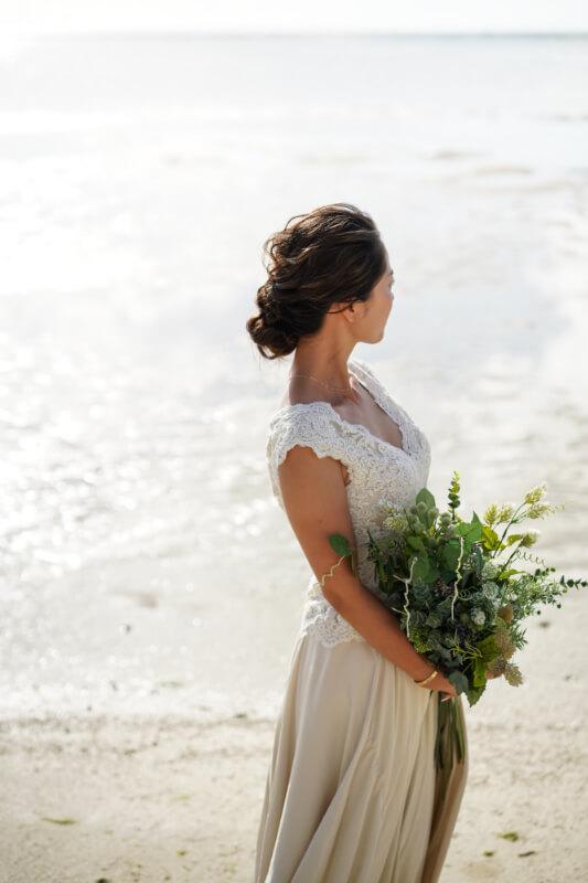 グアムの海でレースのカジュアルなドレスをグリーンのブーケを持っている花嫁