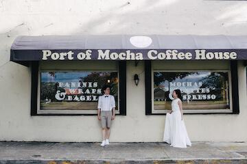 グアムの可愛いカフェをバックにウェディングドレスとタキシードでポージングする2人