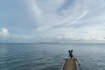 海の先端まで繋がる道に座る新郎新婦