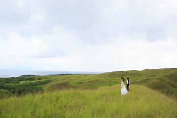 グアムの大草原にドレスとタキシードで立つふたり