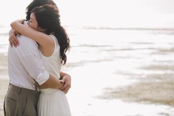 海で抱き合う夫婦