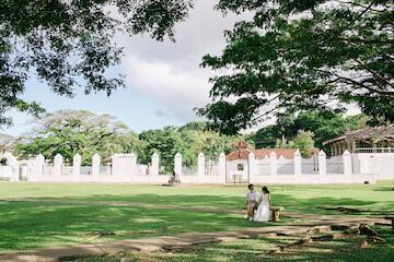 グアムのスペインの公園を歩く新婚夫婦
