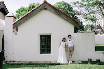 グアムスペイン村の可愛い家の前で笑顔のカップル