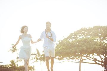 ワイキキビーチを白で合わせたウェディング衣装を着て駆け抜けてるふたり