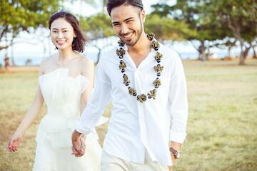 アラモアナビーチでココナッツのレイをかけた新郎の手を繋いで笑顔の新婦