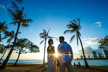 アラモアナビーチのサンセットとヤシの木と新郎新婦の後ろ姿