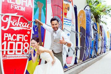 ワイキキビーチで有名なサーフロッカーの前でポーズする新郎新婦