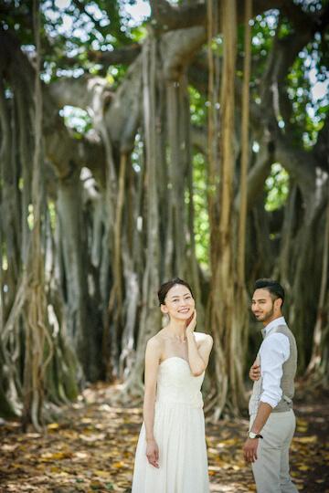 カピオラニパークのバニヤンツリーの前でウェディング写真を撮影する2人