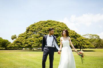 この木なんの木の前でタキシードとドレスを着て撮影