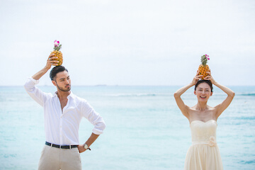 パイナップルを頭の上に乗せてポーズを取っている新郎新婦