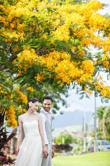 ハワイならではの花の前でフォトウェディングを楽しむふたり