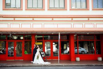 ハワイのダウンタウンの赤い建物の前を歩くふたり