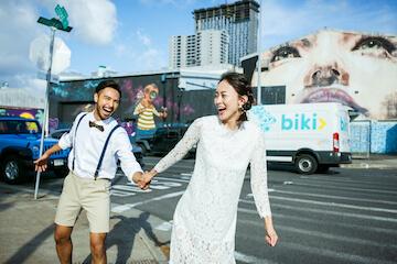 ハワイのウォールアートの大きな壁画の前で手を繋いで笑顔のカップル